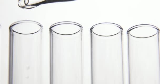 Laboratorní test. Odpipetovat průhledné chemikálie do čtyř zkumavek na bílém podkladu. Koncepce chemického průmyslu a lékařství.