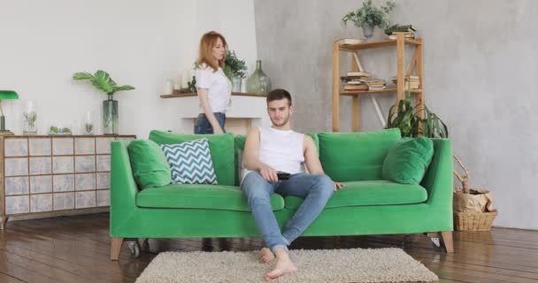 junges Paar im Wohnzimmer auf grünem Sofa, Mann will fernsehen, Frau umarmt ihn.