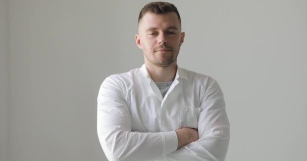Man orvos fehér kabát keresztbe karokkal mosolyog a fehér háttér.