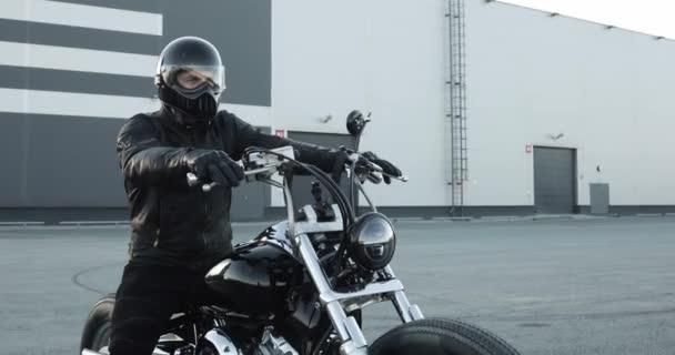 Motorkářka na motorce přijela do garáže, zastavila se a sundala si helmu.