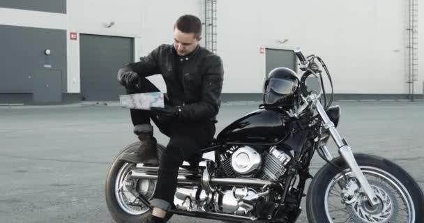 Biker na motorce sedí a dívá se na mapu, která si vybírá trasu svého výletu.