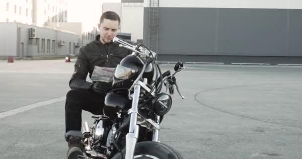 Motorkářka sedí na motorce a dívá se na mapu a vybírá si místo na výlet.
