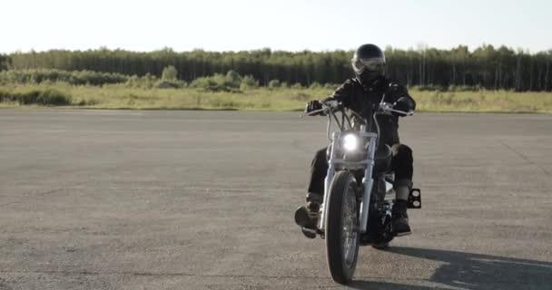 Mladý muž jede na motorce v helmici na silnici, na předním pohledu.
