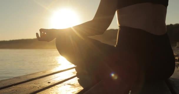 Mädchen meditiert in Lotus Pose auf Fluss hält Hände in namaste Mudra bei Sonnenuntergang.