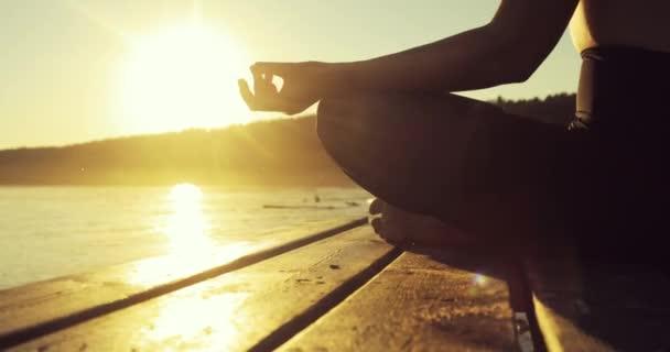 Nő meditál a lótusz pózol a folyón tartja kezében Namaste mudrában naplementekor.