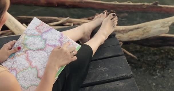 Žena míří na trasu k cíli, která sedí na molu řeky, mapka.