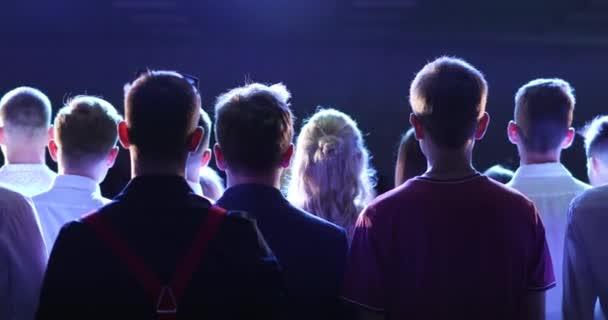 Tömeg az emberek rajongók zenei koncert kék fény a reflektorfényben, vissza megtekintéséhez.