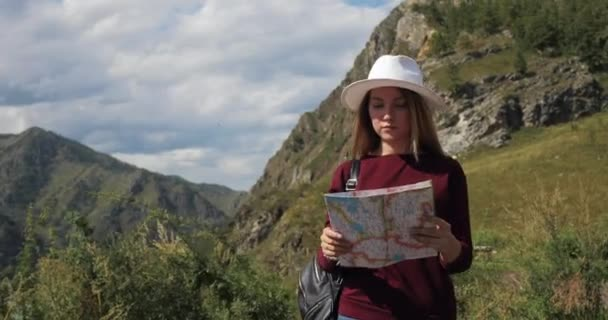 Woman traveller with map hiking in mountains valley on a route in national park.