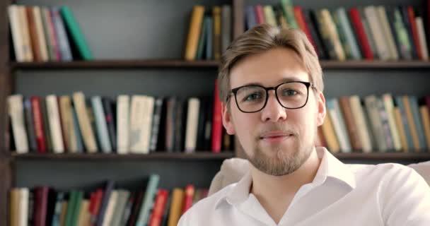 Férfi tanár vagy szemüveges diák az Egyetemi Könyvtárban kamerát néz.