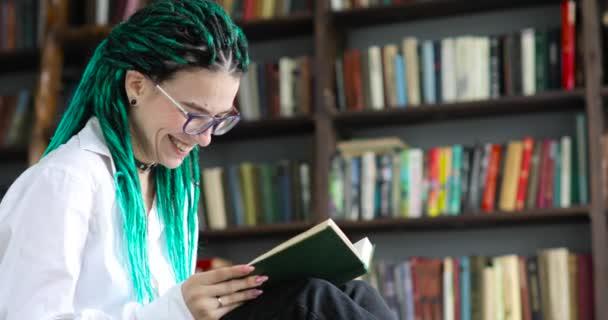 Portré nevető lány diák zöld raszta olvassa könyvet a könyvtárban.