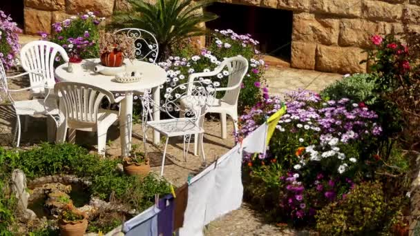 Bedding, which is dried after washing on the background of garden flowers and plastic table and chairs.