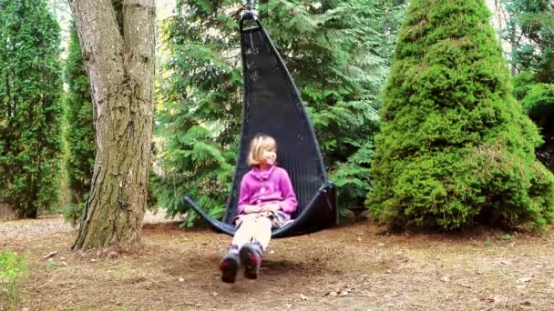 Little beautiful girl on black rocking chair hangs on tree branch in wooded homestead.