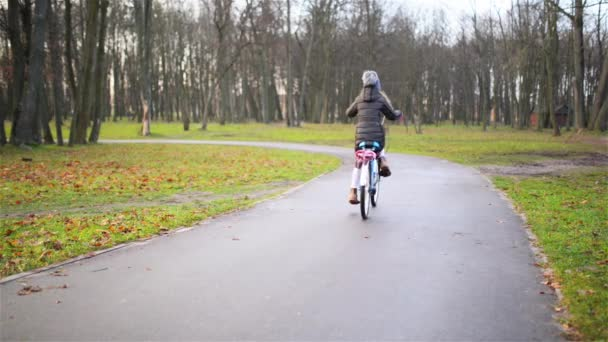 Small beautiful girl rides bicycle through autumn city park.