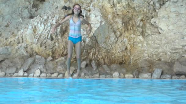 Slow Motion: Little beautiful girl jumping into pool with clear water.