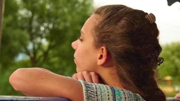 Mladá dívka jezdí na palubě lodi na procházku podél řeky a dívá na pobřežní krajiny.
