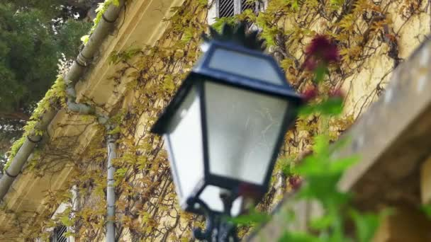 Focus transition: An ancient street lantern on the background of an old stone building.