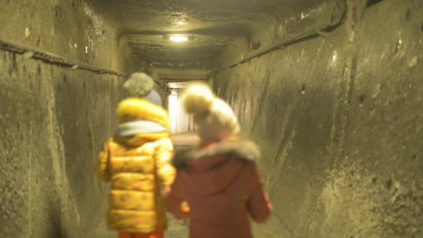 Two beautiful little girls in winter costumes travel in Wieliczka Salt Cave in Krakow Voivodeship in Poland.