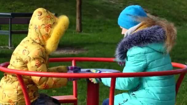 Two beautiful little girls on swing in autumn city park.