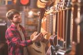 Mladý hudebník výběrem kytary v obchod s hudbou
