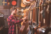 Photo Young musician choosing a guitar in a music store