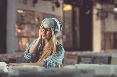 Young girl listening to music with headphones in music store