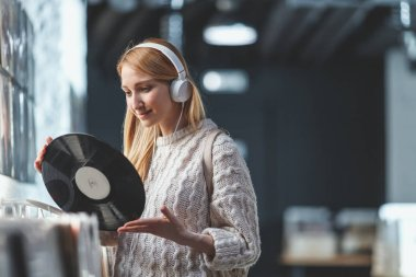 Young girl with a vinyl record in the music store