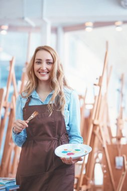 Smiling artist with a palette in the art store