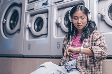 Waiting woman with headphones in the laundry