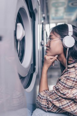 Attractive young girl with headphones in the laundry