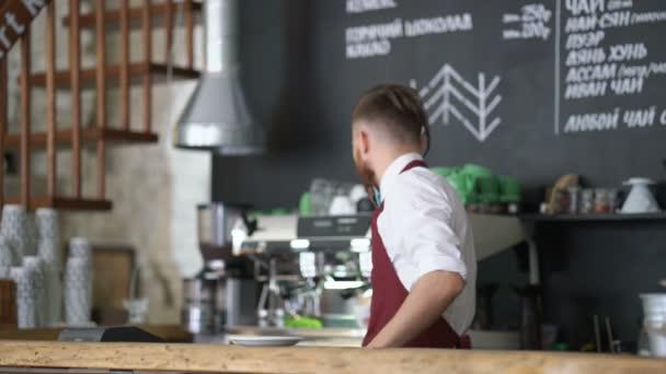 Junger Kellner bereitet Kaffee im Café zu