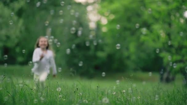 Běh dívka s mýdlovými bublinami venku