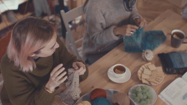 Smiling young women knitting in studio