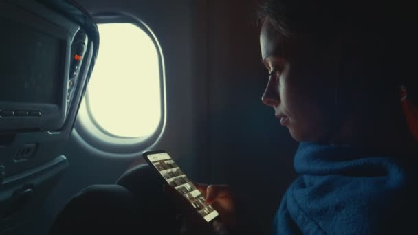 Young girl with a phone by the window in the plane
