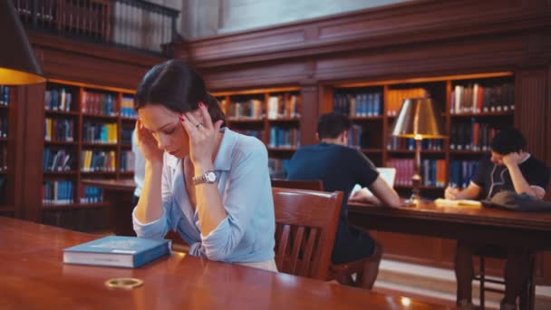 Young woman with headache in the library