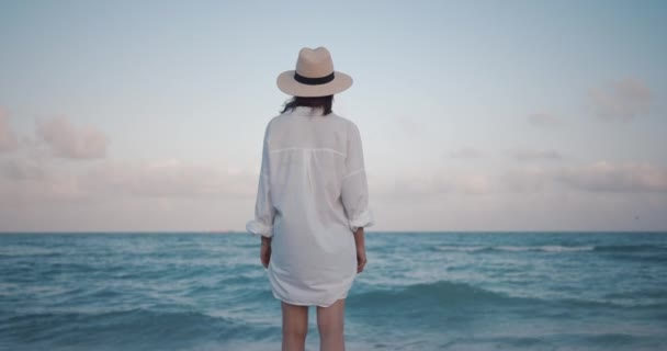 Young girl in a hat by the sea, slow motion
