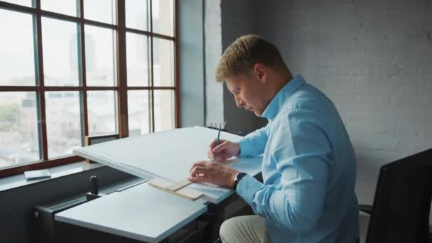 Young professional drawing construction plan by the window