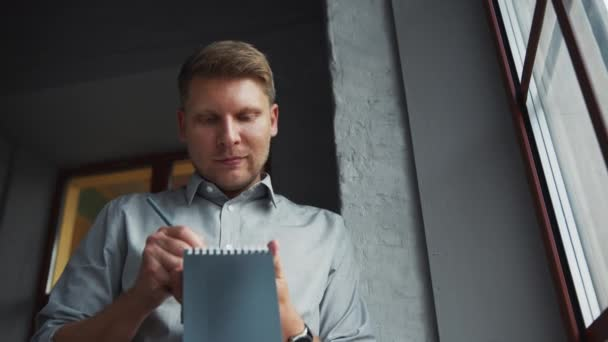 Young businessman with a notepad in the office