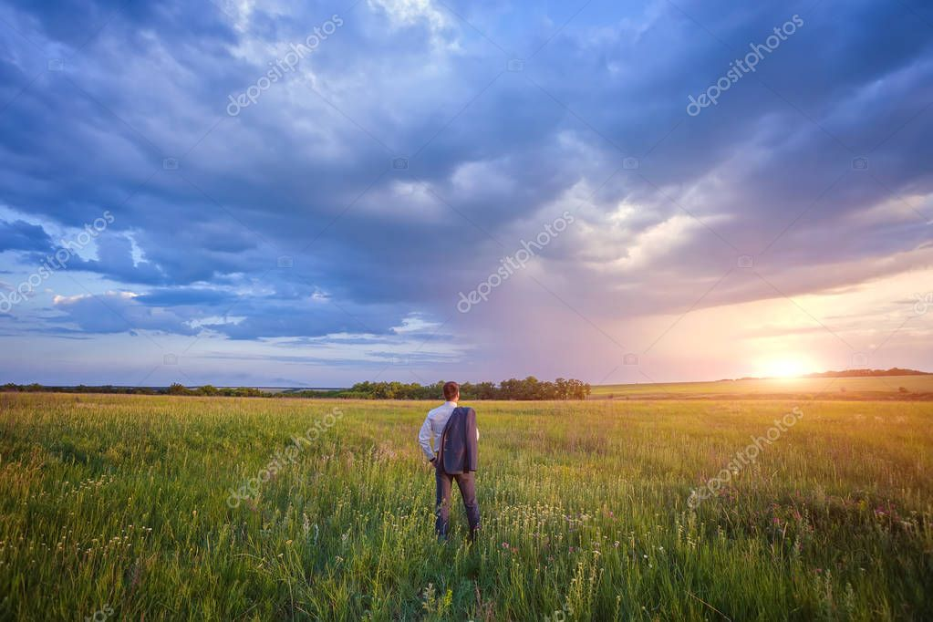 Businessman in elegant suit with his jacket hanging over his shoulder standing in field looking into the distance under a majestic evening sky with a setting sun.