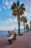 Písečná pláž Konyaalti a retro skútr při západu slunce, Antalya, Turecko středomořské pobřeží