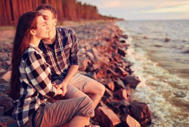 stylish hipster couple kissing at lake. man and woman embracing, in love relaxing in summer park, picnic date. girl in fashionable modern dress and straw hat . rustic wedding concept