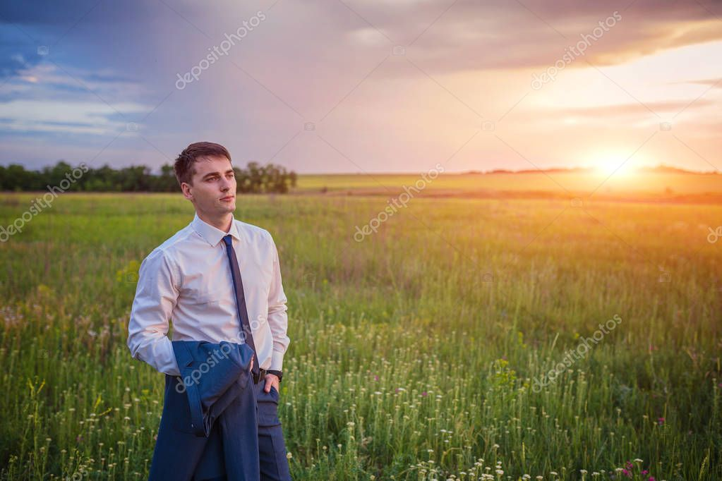 Businessman in elegant suit with his jacket hanging over his shoulder standing in field