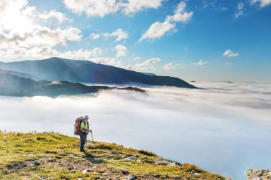 Young woman with backpack travels in mountains