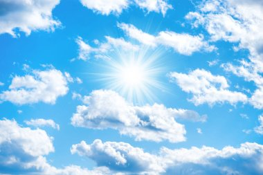 Sun with sun rays and clouds on blue sky as nature background
