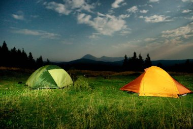 Twp illuminated camping tents on a field at night