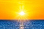 Photo Beautiful sunset sea landscape with blue sea water and sun on yellow clear sky