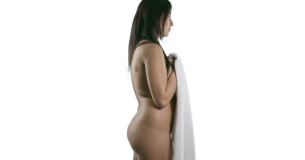 Boční pohled na nahé ženy, pokrývající její tělo ručníkem.