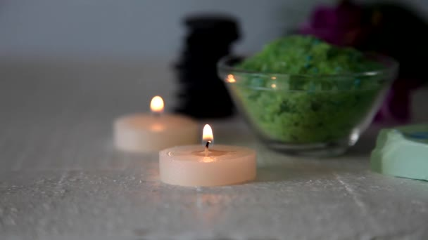 Hořící svíčky, wellness kameny, mořské soli a orchidej na stůl