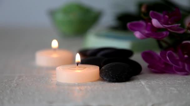Hořící svíčky, wellness kameny, mořské soli a orchidej na stůl.