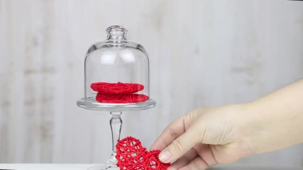 Female hand puts the red hearts in a transparent vase. Gift for Valentine's Day.