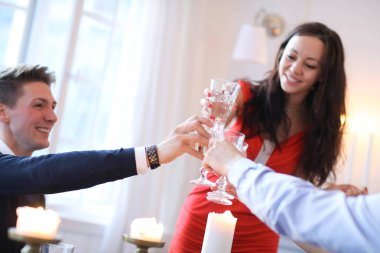 happy young couple celebrating Christmas at home and clanging glasses together